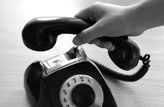 Mano descolgando teléfono antiguo.